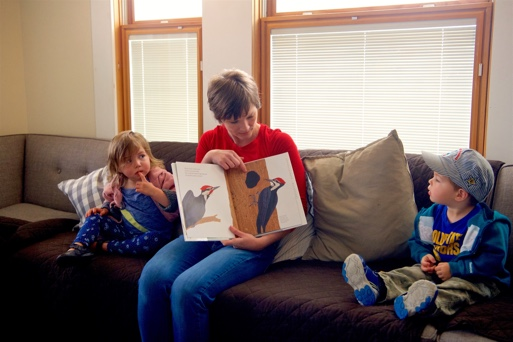 Devon reading a book about birds to two children