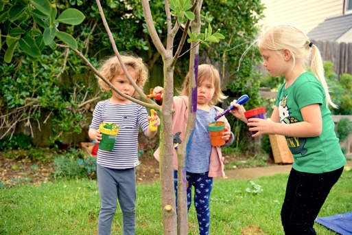 Children painting the branches of a lemon tree